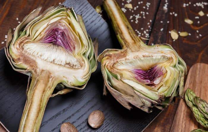 Image of artichoke halves on a black cutting board