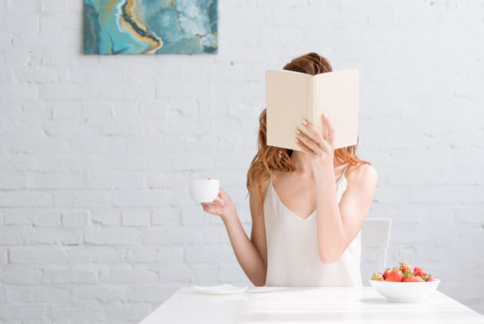 Woman with cup of coffee and bowl of strawberries covering face with book at home