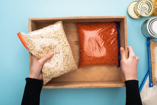 Cropped view of woman packing groats in wooden box on blue background, food donation concept